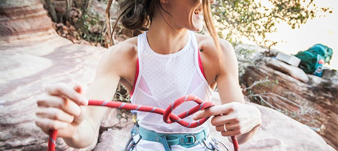 girl tying a rope for rock climbing; Photo by Brooke Anderson on Unsplash