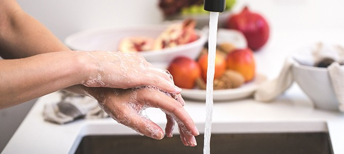 person washing their hands at a kitchen sink