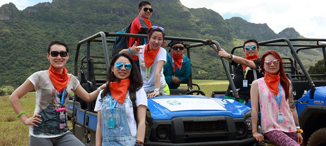 Nu Skin Sales Leaders from Greater China pose in front of off-road vehicles while they explore famous movie sets in Hawaii.