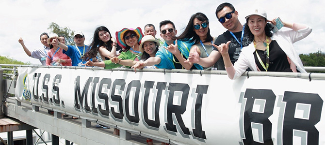 Greater China Sales Leaders of Nu Skin pose for a picture on their way onto the USS Missouri.