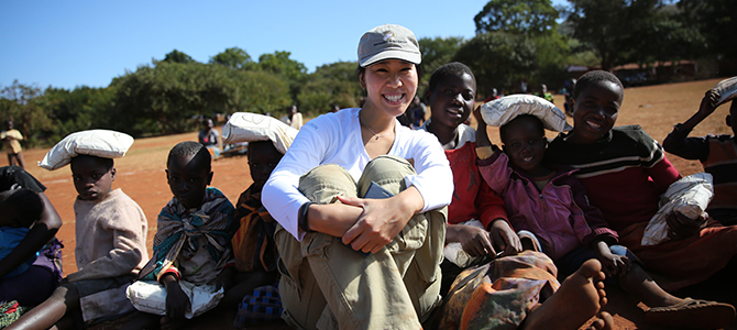 A Nu Skin sales leader sits with Malawi children as they receive bags of VitaMeal.